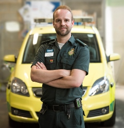 Alex in LAS uniform stood in front of an ambulance car