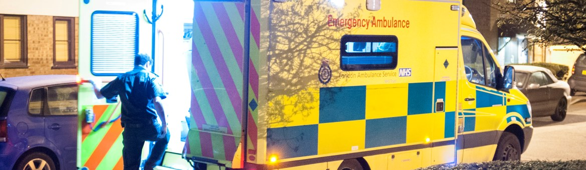 A medic steps into the back of an open ambulance rear door