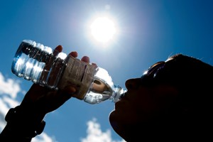 woman drinks from bottle of water in hot weather