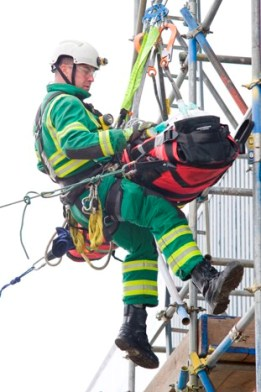 A member of ambulance staff lowers a patient on a stretcher from the top of scaffolding during Exercise Amber