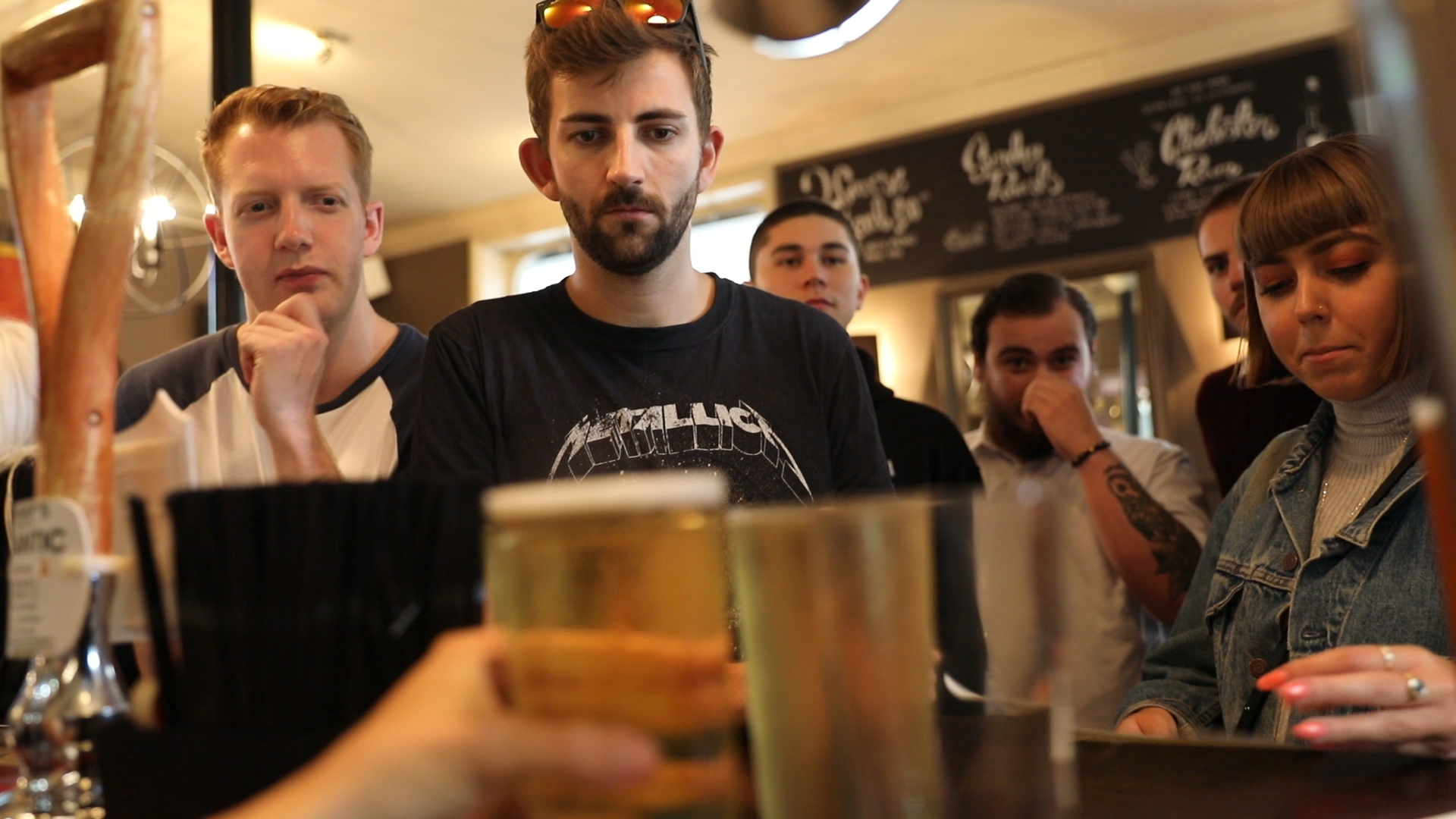 Young people ordering beers in a pub