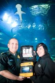 Community Defibrillation Officer Martin Bullock and London Aquarium Duty Manager Laura Bristow with a defibrillator