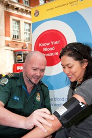A member of staff checks someone's blood pressure at Waterloo train station
