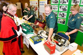 The Mayor of Islington looking at defibrillators from past and present at the Islington community health fair