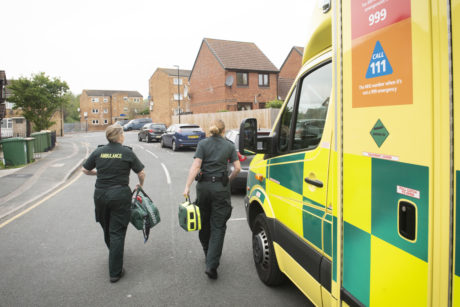 A photograph of an ambulance with two female medics in green uniform walking away carrying kit bags
