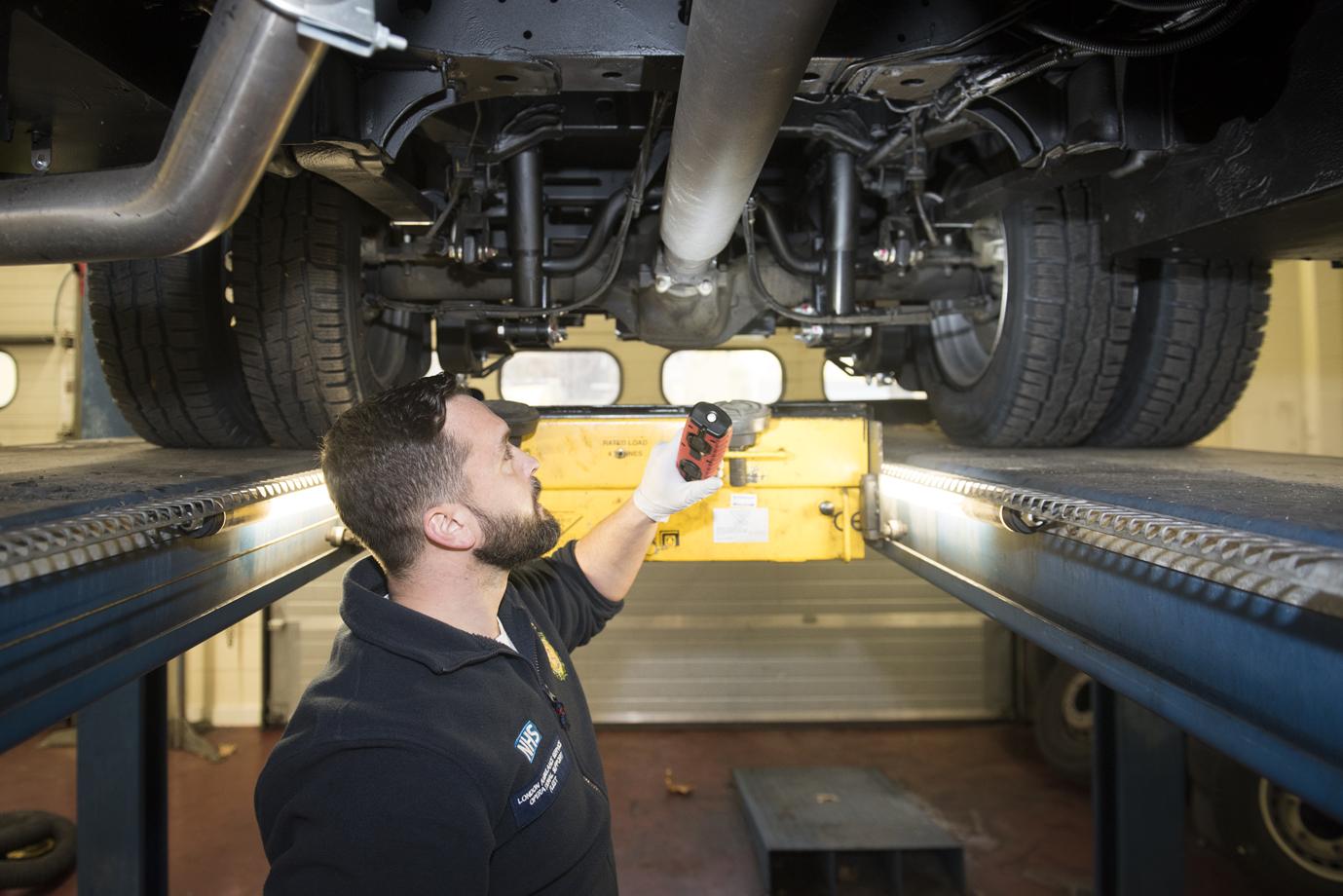 Workshop staff member looks beneath ambulance on ramp