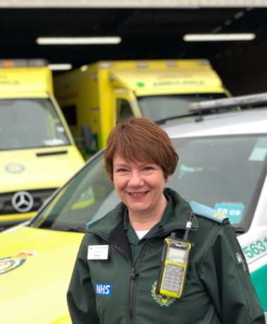 Debbie stood in front of an ambulance car and two ambulances in her green Service uniform