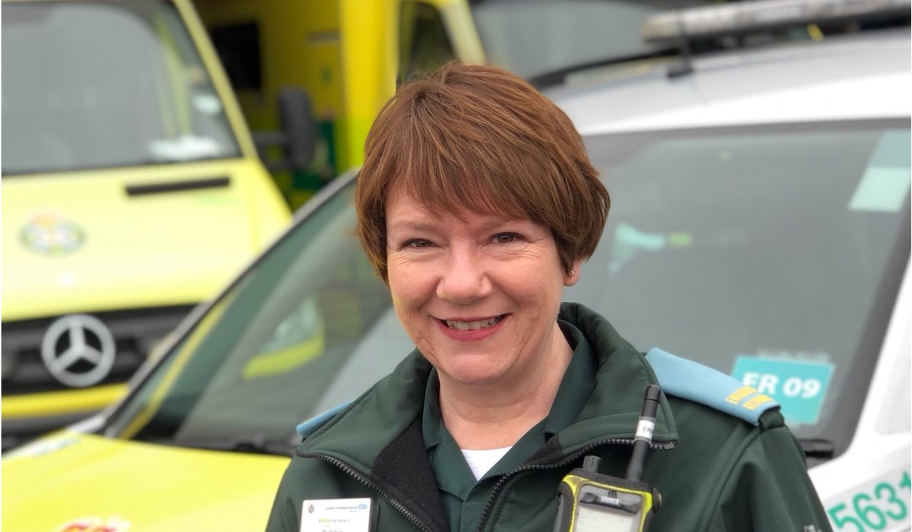 Debbie in uniform in front of ambulance vehicles