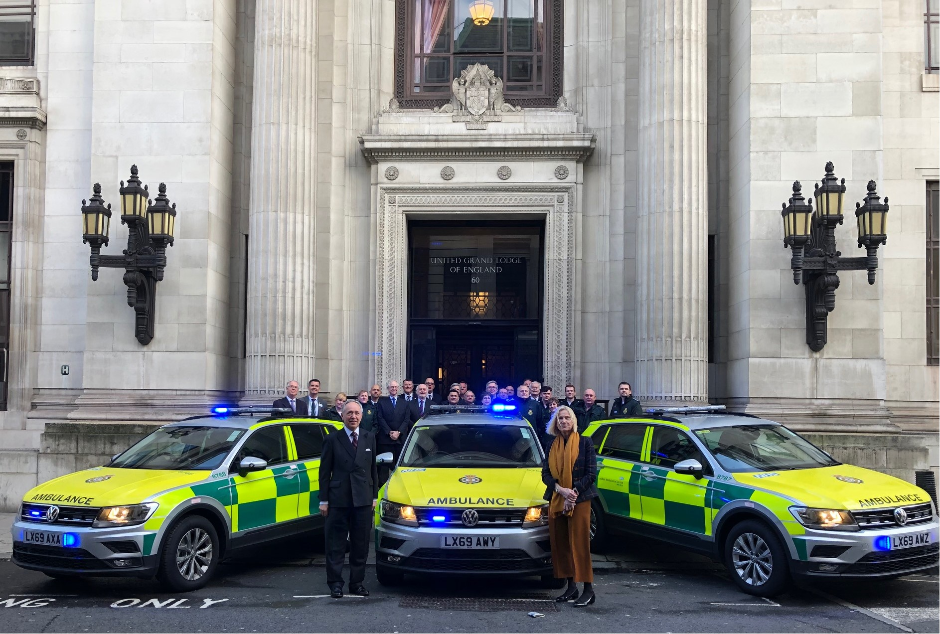 Three new response cars parked in front of the Freemasons building with people stood behind