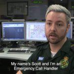 Scott in uniform in front of control room screens