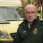 Garrett Emmerson in Service jacket in front of ambulances