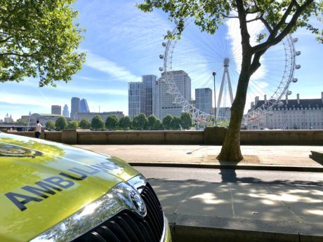 ambulance car parked with London Eye and blue skies in background