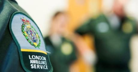 The London Ambulance logo on the green uniform