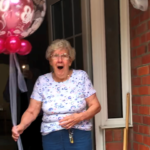 Mike's grandmother holding balloon looking happy and surprised