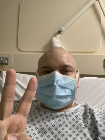 Richard in hospital with mask giving victory sign