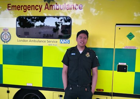 Sheqal Lim stood in front of an ambulance in green uniform