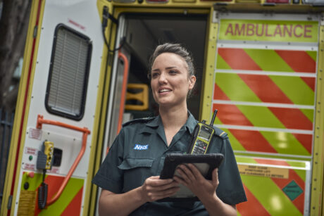 A paramedic holding an iPad in front of an ambulance