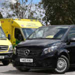 Black Mercendes van next to two ambulances
