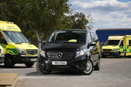 A black mercedes van in a car park with ambulances