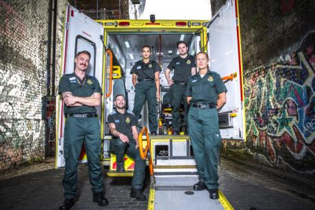 Group of ambulance staff by rear of open ambulance