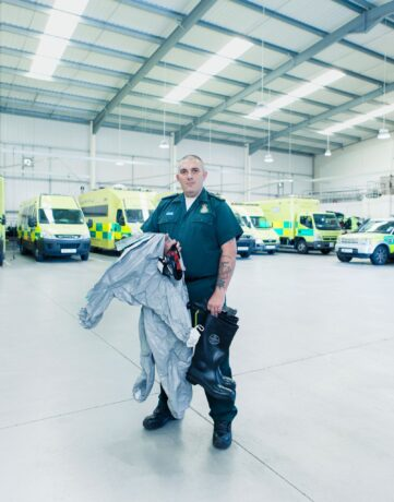 Simon Woodmore with hazardous area clothing with ambulances in background