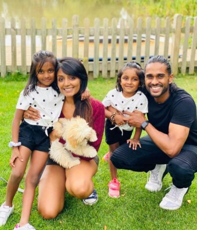 Avaana and her family crouched smiling in a field