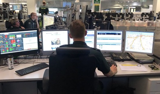 Peter shown from behind at his desk with multiple computer screens