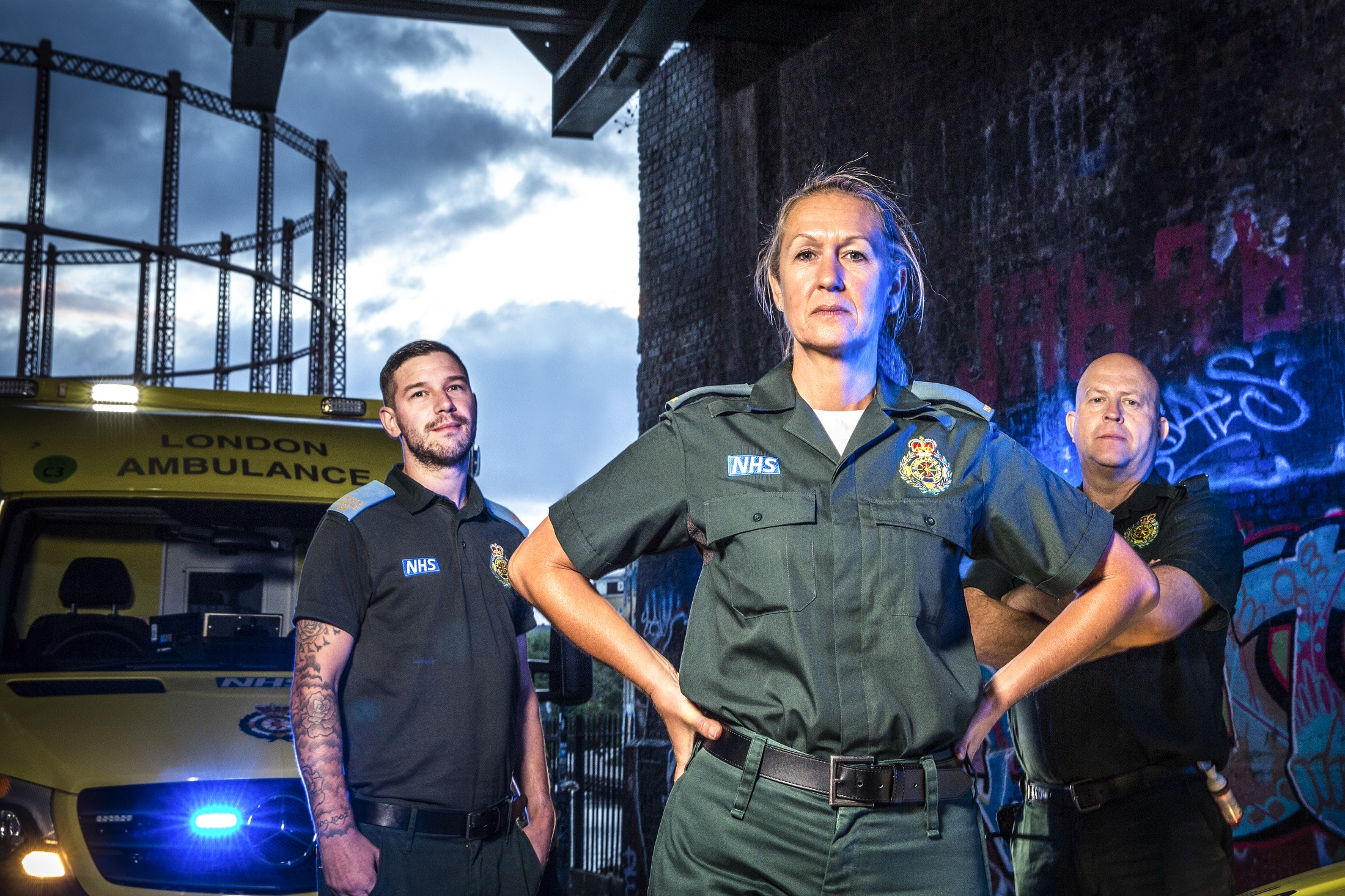 Stuart, Rachel and Pete stood in front on an ambulance in a dark setting