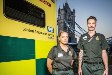 Orani and Adam next to an ambulance with Tower Bridge in background