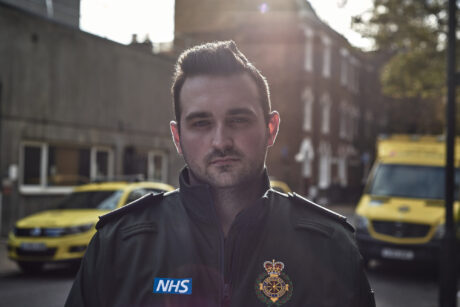 Kieran stands with an ambulance car and ambulance behind him