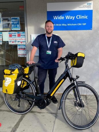 A paramedic stood in front of a clinic with his electric bike
