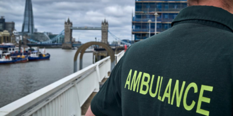 Medic shown from behind with the word Ambulance on their top visible and with Tower Bridge in the background