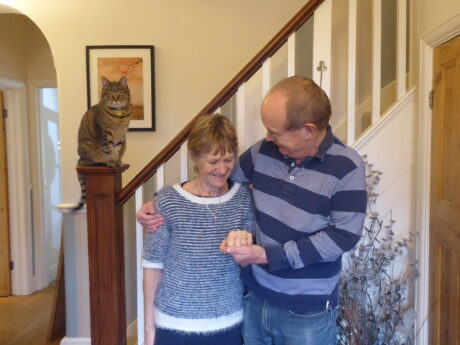 Sally and Brian at home with arms round each other