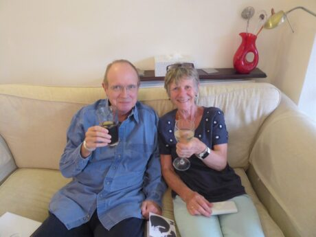 Brian and Sally sat on a sofa raising a glass eacg