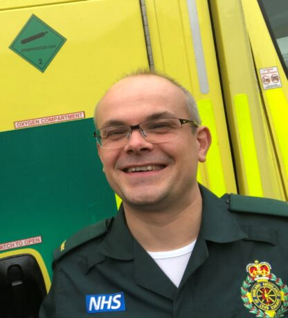 Dr Martin in ambulance uniform stood in front of the side of an ambulance
