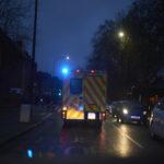 an ambulance with flashing lights on a dark street