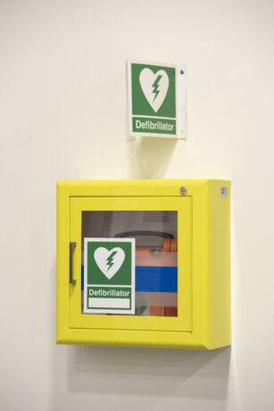 A defibrillator in a yellow cabinet attached to a wall