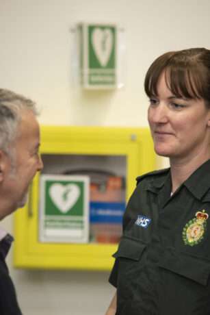 A LAS medic in uniform speaks to a man in front of a defibrillator cabinet