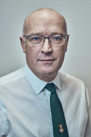 Portrait shot of Garrett Emmerson in white shirt with green tie with LAS crest