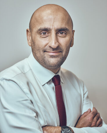 Khadir Meer in a white shirt and red tie in a portrait photograph