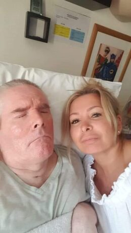 Paul lying in a hospital bed with Ellie by his side