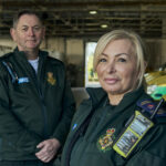 Dave and Ellie stood in LAS uniform in front of a row of ambulances