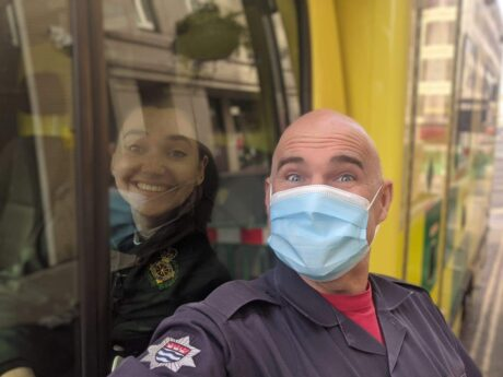 Firefighter Martin stood with a mask next to ambulance cab window with Rebecca shown behind the window glass smiling