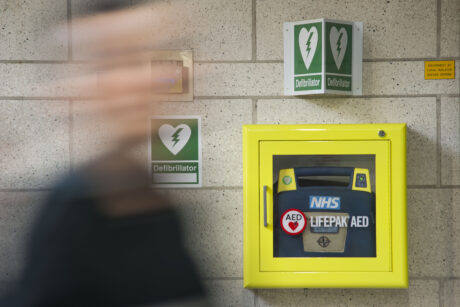 A defibrillator in a yellow cabinet attached to a wall as a person walks past