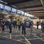 A number of ambulance staff and Chief Midwifery Officer stood in an ambulance garage