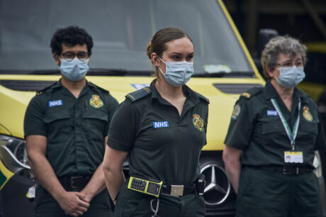 Uniformed LAS staff in front of ambulances observing the minute silence