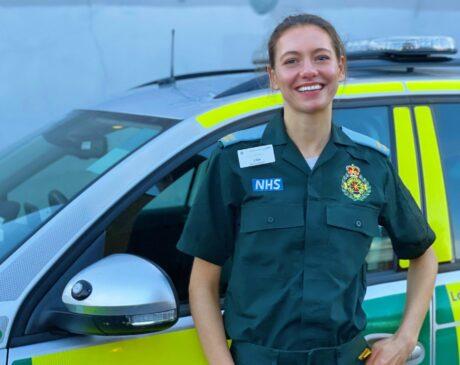 Elisabeth stood in ER green LAS uniform in front of a response car