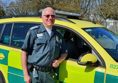Ian stood in uniform next to an LAS response car