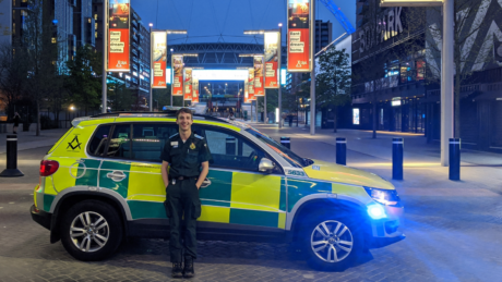 James stood in front of an ambulance car with Wembley Stadium in background