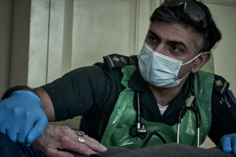 A paramedic with a mask and apron comforting a patient